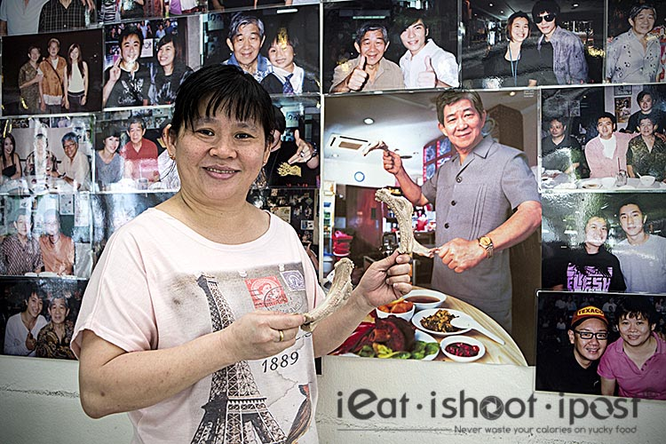 Chui Chui posing with the photo of her father in the background